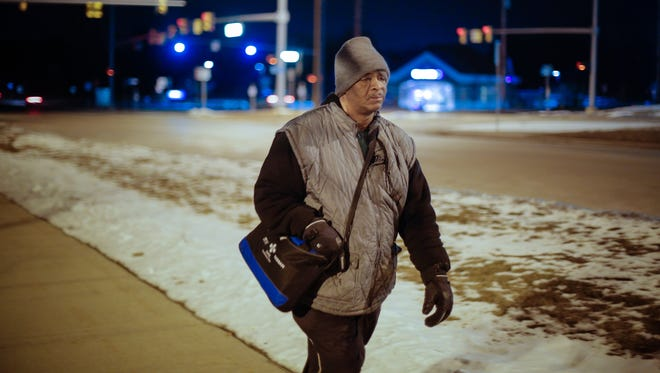 James Robertson, 56, of Detroit, makes his way along Crooks Road after working his shift at Schain Mold & Engineering in Rochester Hills on Friday, Jan. 9, 2015.