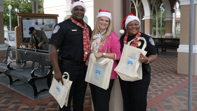Fort Pierce Police Deputy Chief Kenny Norris, St. Lucie County Commissioner Cathy Townsend and Fort Pierce Police Chief Diane Hobley-Burney enjoyed playing Santa as they handed out Transit Swag Bags to riders of the Treasure Coast Connector.