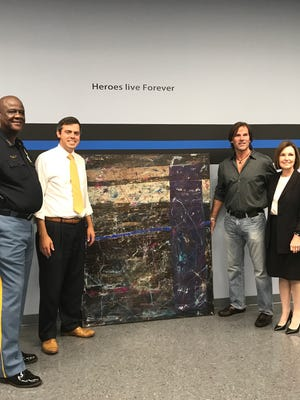 """From left, Hattiesburg police Chief Anthony Parker, Mayor Toby Barker, artist Robert Williams and Forrest-Perry District Attorney Patricia Burchell stand with """"The Thin Blue Line,"""" a painting Williams donated to HPD to honor fallen officers Liquori Tate and Benjamin J. Deen."""