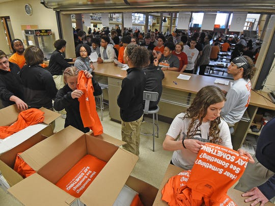 Eleventh graders Hailey Jacobs and Megan Supron try to keep up Tuesday morning with the demand for t-shirts. Mansfield Senior High School students recieved a free T-shirts during lunch today for agreeing to remain inside the school Wednesday morning and not participate in the National School Walk-Out Day.