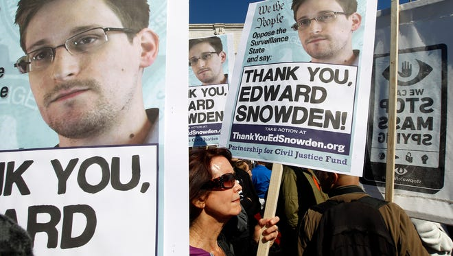Demonstrators hold signs bearing the face of NSA whistle-blower Edward Snowden while protesting outside of the Capitol.