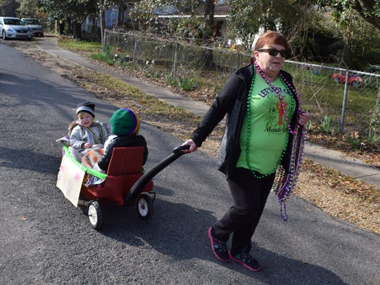 Debra Budrow (front) pulls a wagon with her grandchildren Isabella and Virginia Sanders as they participate in the 11th annual Krewe of Pollock Children's Mardi Gras parade held Saturday in Pollock. Budrow said this the fifth time they have participated in the parade. The parade started in Foster Park and wound around the neighborhood for a few blocks.