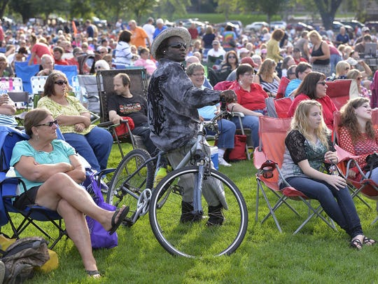 The crowd, gathered in lawn chairs and even on a bicycle, watches as the concert starts at Summertime by George! in August, 2014.