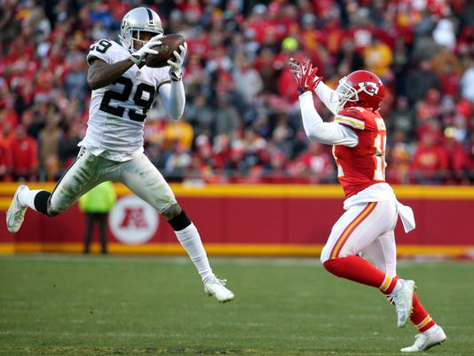 Oakland Raiders cornerback David Amerson (29) intercepts a pass intended for Kansas City Chiefs wide receiver Albert Wilson (12) for a touchdown, during the first half of an NFL football game in Kansas City, Mo., Sunday, Jan. 3, 2016. (AP Photo/Charlie Riedel)