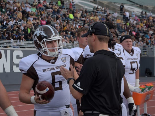 Western Michigan head coach Tim Lester (right) talks with quarterback Reece Goddard (6) before be subbed in for injured Jon Wassink on Saturday in Ypsilanti.