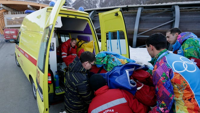 A track worker is loaded into an ambulance after he was injured when a forerunner bobsled hit him just before the start of the men's two-man bobsled training.