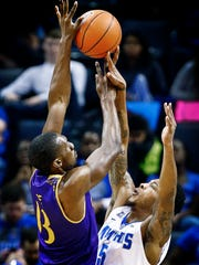 University of Memphis guard Markel Crawford (right) blocks the shot of East Carolina University forward Michel Nzege (left) during first half action at FedExForum.