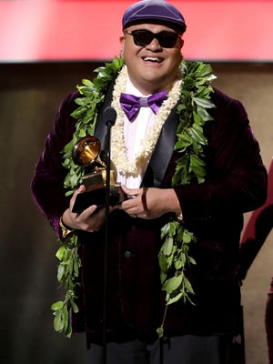 """Kalani Pe'a accepts the award for best regional roots music album for """"E Walea"""" at the 59th annual Grammy Awards on Sunday."""