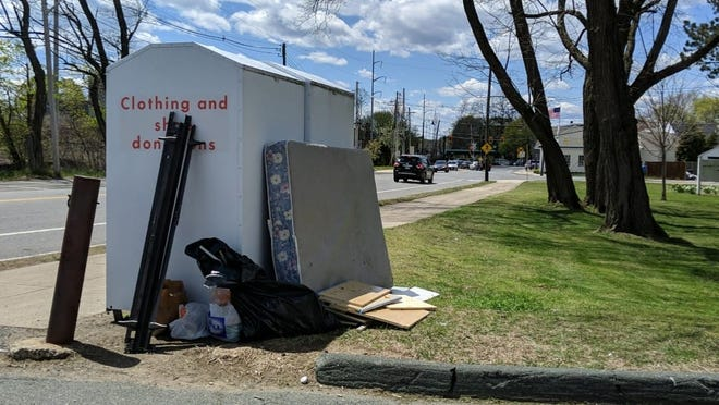 Items like mattresses and other unwanted home goods have been left alongside the textile recycling bins located outside the former Briscoe Middle School building.