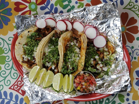 Four tacos al pastor is made with corn tortillas, topped with cilantro and onions, served with pico de gallo, salsa verde, hot salsa and radishes.