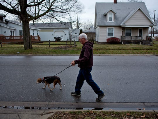 "Bill Kessler walks his five-year-old Beagle, Daisy, Wednesday Dec. 23, 2015 along Conner Street in Port Huron. Kessler was walking Daisy Tuesday afternoon in the 2900 block of North Boulevard when a larger dog charged and attacked her. Kessler shot and killed the dog after pepper-spraying and kicking the dog failed to stop the attack. ""I was terrified,"" Kessler said. Daisy sustained several puncture wounds and is recovering."