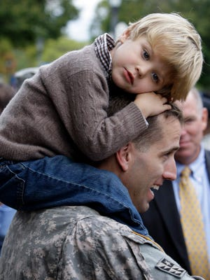Capt. Beau Biden carries his son Hunter, 3, on his shoulders after an official welcome home ceremony for members of the Delaware Army National Guard 261st Signal Brigade in Dover, Del.. on Sept. 30, 2009.