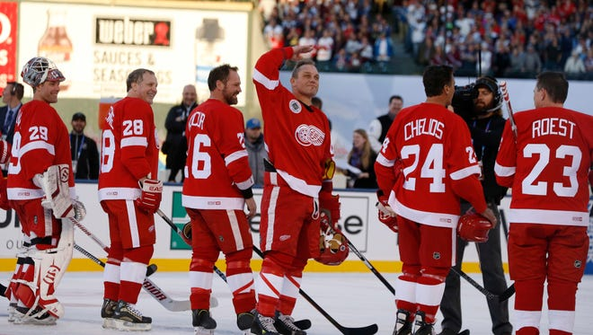 Red Wings right wing Darren McCarty, center, salutes the crowd while being introduced before an alumni game against the Colorado Avalanche at Coors Field in Denver on Friday.
