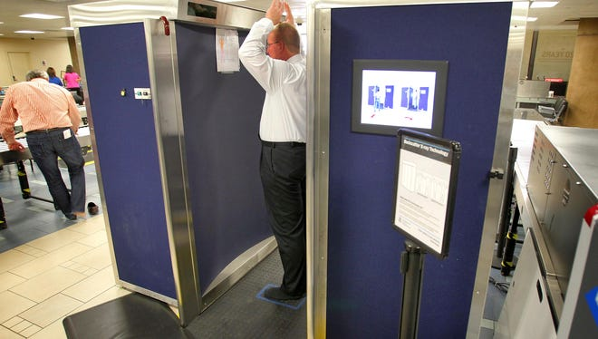 A passenger goes through a scanning machine at Sky Harbor International Airport in Phoenix.