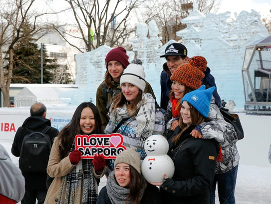 Foreign tourists pose for a photo in front of an ice