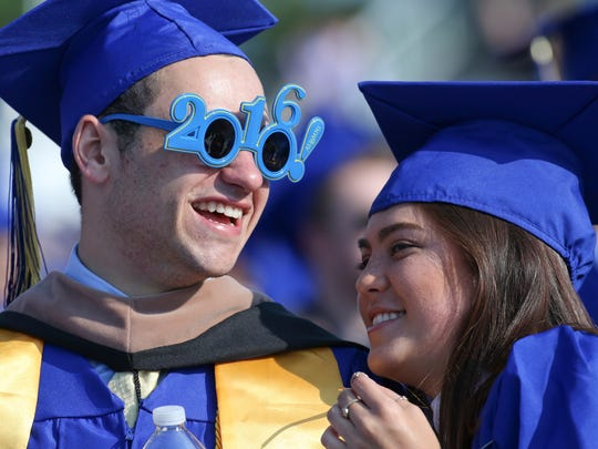 Graduates John Francis Cooney III of Washington Township, NJ, and Melina Roldan of Clayton, NJ wait for the opening of ceremonies after processional as the University of Delaware confers degrees on about 5800 students during commencement at Delaware Stadium Saturday.