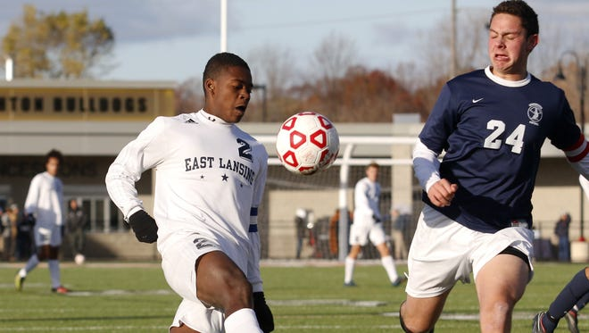 East Lansing's DeJuan Jones, left, kicks against Bloomfield Hills Cranbrook-Kingswood's Stephen Luckoff (24) during their MHSAA Division 2 championship game Saturday, Nov. 1, 2014, in Brighton, Mich. East Lansing won 4-3 in overtime.
