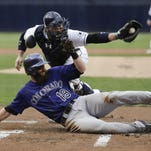 Colorado Rockies' Charlie Blackmon, below, is tagged out at home by San Diego Padres catcher Derek Norris during the first inning of a baseball game Wednesday, Sept. 9, 2015, in San Diego. (AP Photo/Gregory Bull)
