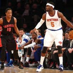 New York Knicks shooting guard Tim Hardaway Jr. (5) controls the ball against Toronto Raptors shooting guard DeMar DeRozan (10) during the first quarter on Saturday at Madison Square Garden.