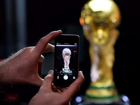 A man takes a picture of the FIFA World Cup trophy on display at Westfield shopping centre in west London on March 14, 2014, as part of its world tour ahead of the Brazil 2014 World Cup.
