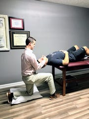 Dr. Scott Holmes works with his patient's neck to figure out what is causing discomfort.