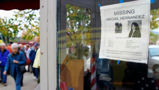 In this Oct. 16, 2013 file photo, tourists walk by an information booth in North Conway, N.H., bearing a poster of missing teenager Abigail Hernandez, 14, who disappeared on Oct. 9, 2013, after leaving school. New Hampshire Attorney General Joseph Foster said Monday, July 21, 2014, that Abigail Hernandez was reunited with her family Sunday evening.