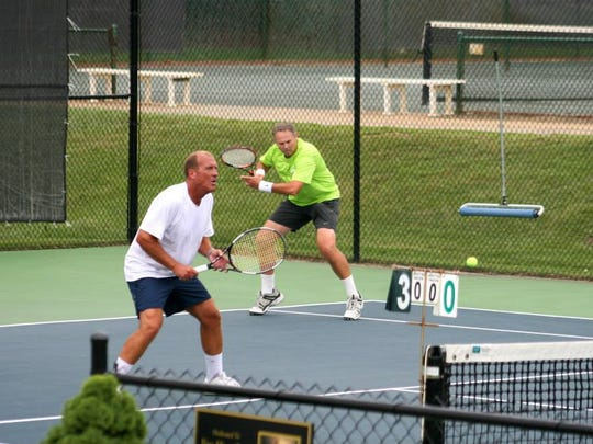 Laneal Vaughn and Jeff Duncan play doubles on the Asheville Racquet Club's outdoor facility. The club's seen 20 percent growth each year since 2014.