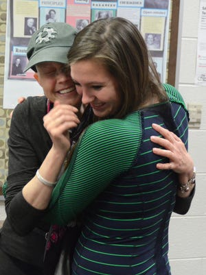 Katherine Purcell hugs Northville High cheerleader Alyssa Corn, after hearing how much the team has done to make her battle with breast cancer easier.
