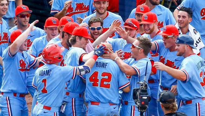 Ole Miss' Tim Rowe (42) is mobbed by his teammates after he hit a two-run home run in the seventh inning of the Rebels' win over LSU Sunday.