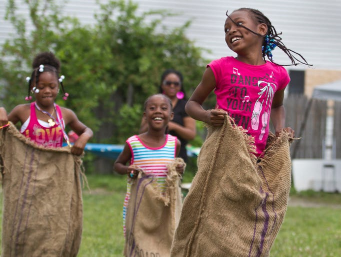 Nalazja Howard, 8, of Asbury Park, right, wins a potato sack race. Have a Super Safe Summer is  a community event held at Springwood Park to introduce families from Asbury Park and surrounding areas to programs available to them throughout the summer months.  Asbury Park, NJ Saturday, June 14, 2014 Doug Hood