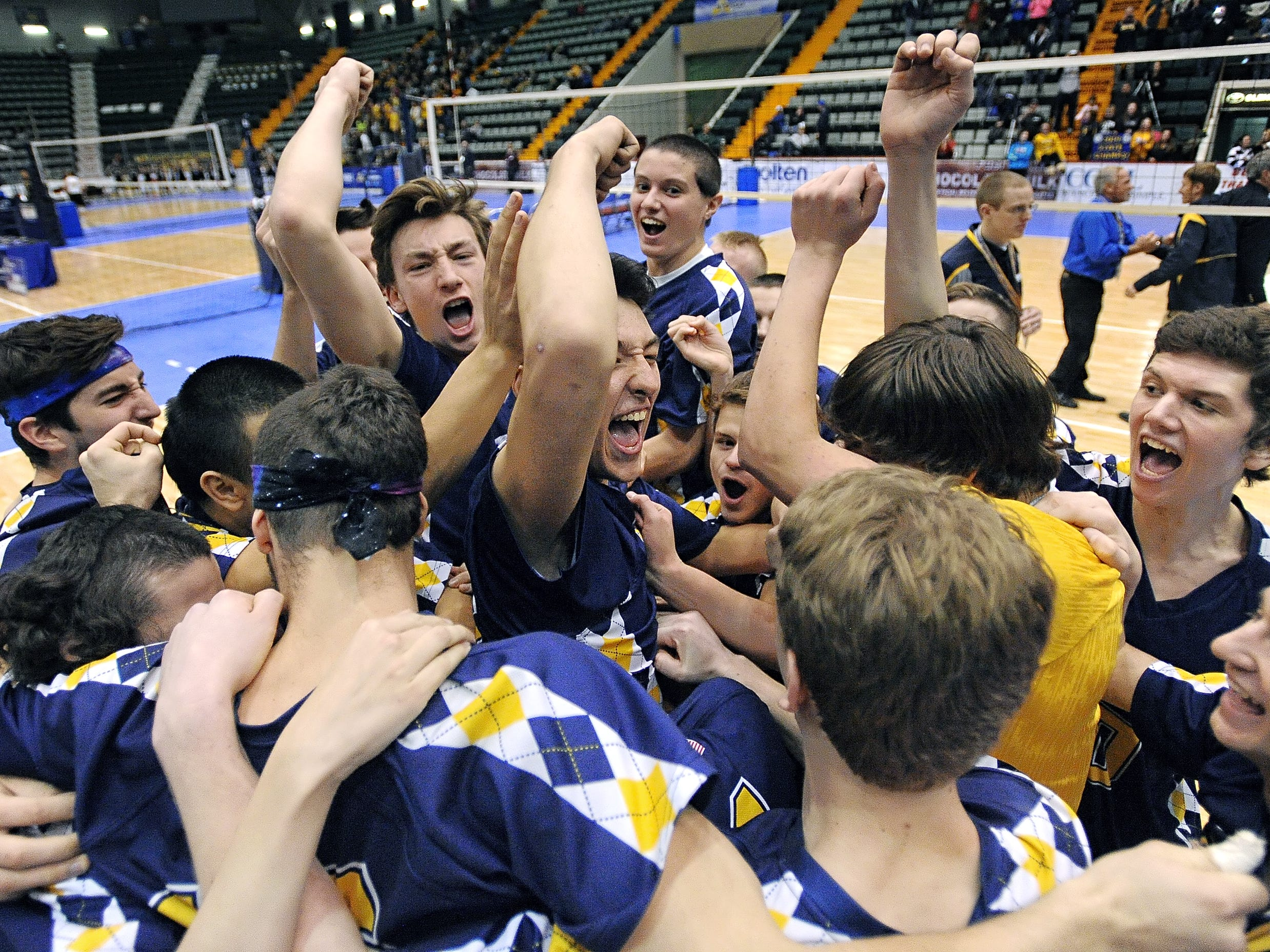 Victor players celebrate following championship point in the Division II final at the NYSPHSAA Boy's Volleyball Championships held at the Glens Falls Civic Center on Friday. Victor beat Eastport-South Manor in three sets (25-12, 25-21, 25-18). ADRIAN KRAUS