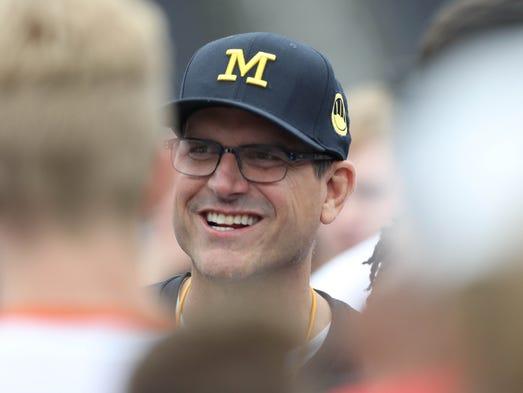 Michigan coach Jim Harbaugh talks to high school players