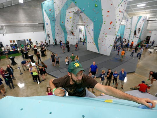 Ryan McClain climbs a bouldering problem on a wall during the grand opening of the Zenith Climbing Center on April 2, 2016.