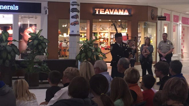 Brandon police chief Dave Kull plays the bagpipes during the sixth annual Project Blue Light event at  the Empire Mall in Sioux Falls.