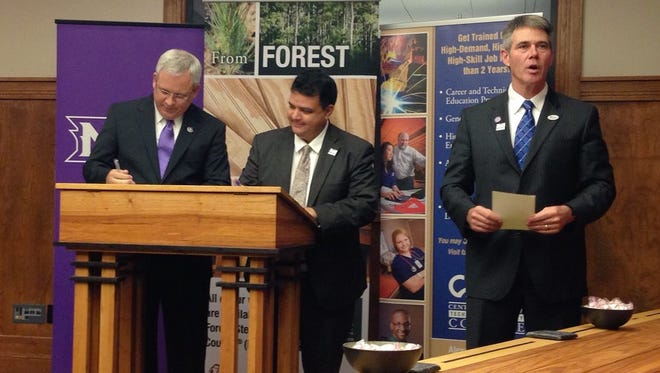 Northwestern State University President Jim Henderson (left) and Central Louisiana Technical Community College Chancellor Jimmy Sawtelle sign an articulation agreement regarding manufacturing courses at the two institutions on Wednesday. Roy O. Martin III (right), president of RoyOMartin, announces how the company will take part in the C4M program next quarter.