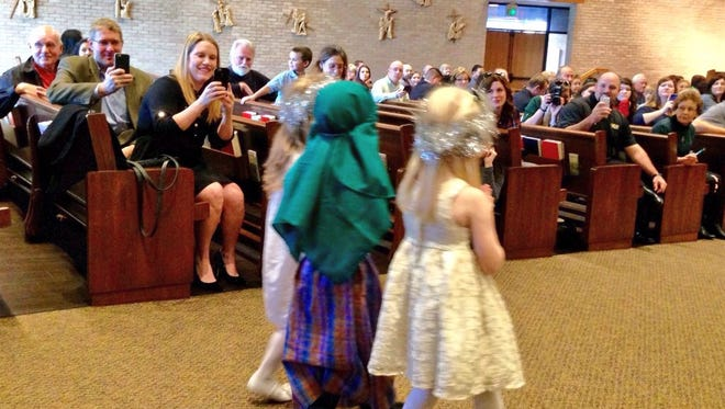 Parents snap photos of their pre-K students during Our Lady of Prompt Succor School's Christmas program Thursday.