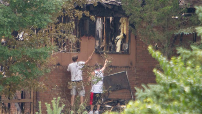 Workers prepare to board up windows of the house on Huskey Court in Brighton Township destroyed by a fire early Tuesday morning which left one resident dead.