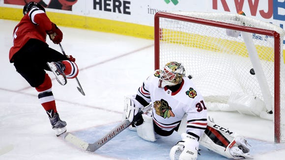 New Jersey Devils left wing Taylor Hall, left, scores a goal against Chicago Blackhawks goalie Anton Forsberg, of Sweden, during the third period of an NHL hockey game, Saturday, Dec. 23, 2017, in Newark, N.J. (AP Photo/Julio Cortez)
