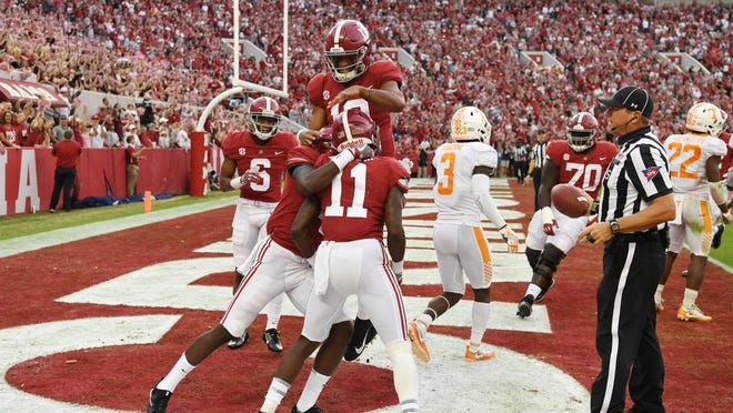 Alabama Crimson Tide wide receiver Henry Ruggs III celebrates his touchdown with quarterback Tua Tagovailoa and other teammates in the end zone against the Tennessee Volunteers.