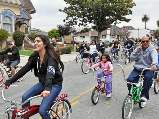 Participants in the fifth annual Burrito Bike Ride stream past the Steinbeck House at the beginning of a leisurely circuit of the city of Salinas.