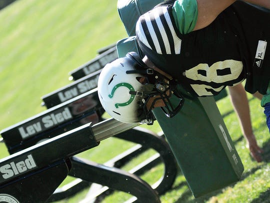 Isaac Roberts hits the blocking sled during practice Wednesday.