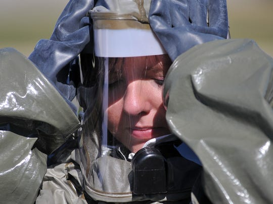 Tech Sgt. Sabrina Roberts puts on her hood during training exercises at the 179th Airlift Wing of the Ohio National Guard base Thursday.  Mitchell Pe Masilun/News Journal