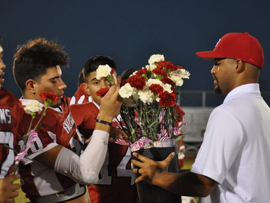 Senior Falcons receive carnations from a Falcon coach