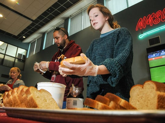 """New Mexico State University student Caroline Stapleton, 19, Phillip Cordero, 36, NMSU facilities technician, and NMSU Office of Sustainability manager joni newcomer make peanut butter and jelly sandwiches on Wednesday at Corbett Center during the """"STOP Hunger with PB&J Event"""" hosted by Sodexo Campus Dining and the Office of Sustainability, Facilities and Services. About 20 volunteers made 800 sandwiches to donate to El Caldito Soup Kitchen."""