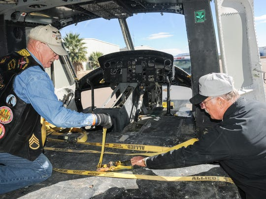 Bruce Fonnest, left, and Jim Haribson strap down a Huey onto a trailer Thursday. The helicopter weighs 4,000 pounds, is approximately 50 feet long and 8-and-a-half feet wide.