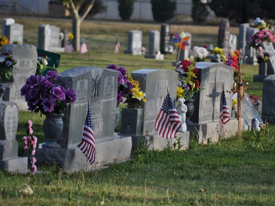 Flags mark the graves of Veterans in Carlsbad Cemetery.