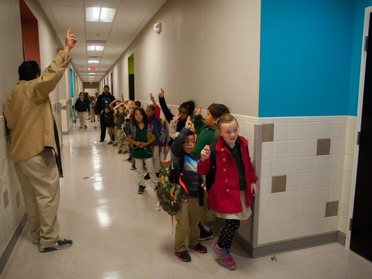 First-grade students line up to go inside their new classroom for the first time at the new J. Paul Taylor Academy campus on West Court Avenue.