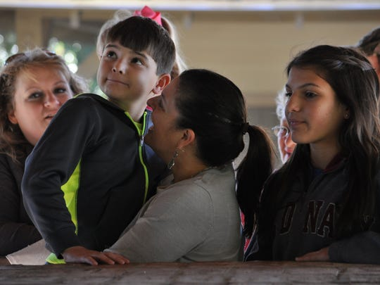 (From left) Ian Hunter along with mom Shannon Chiasson and sister Olivia watch a syrup-making demonstration at the Kent Plantation House on Saturday during Sugar Day.