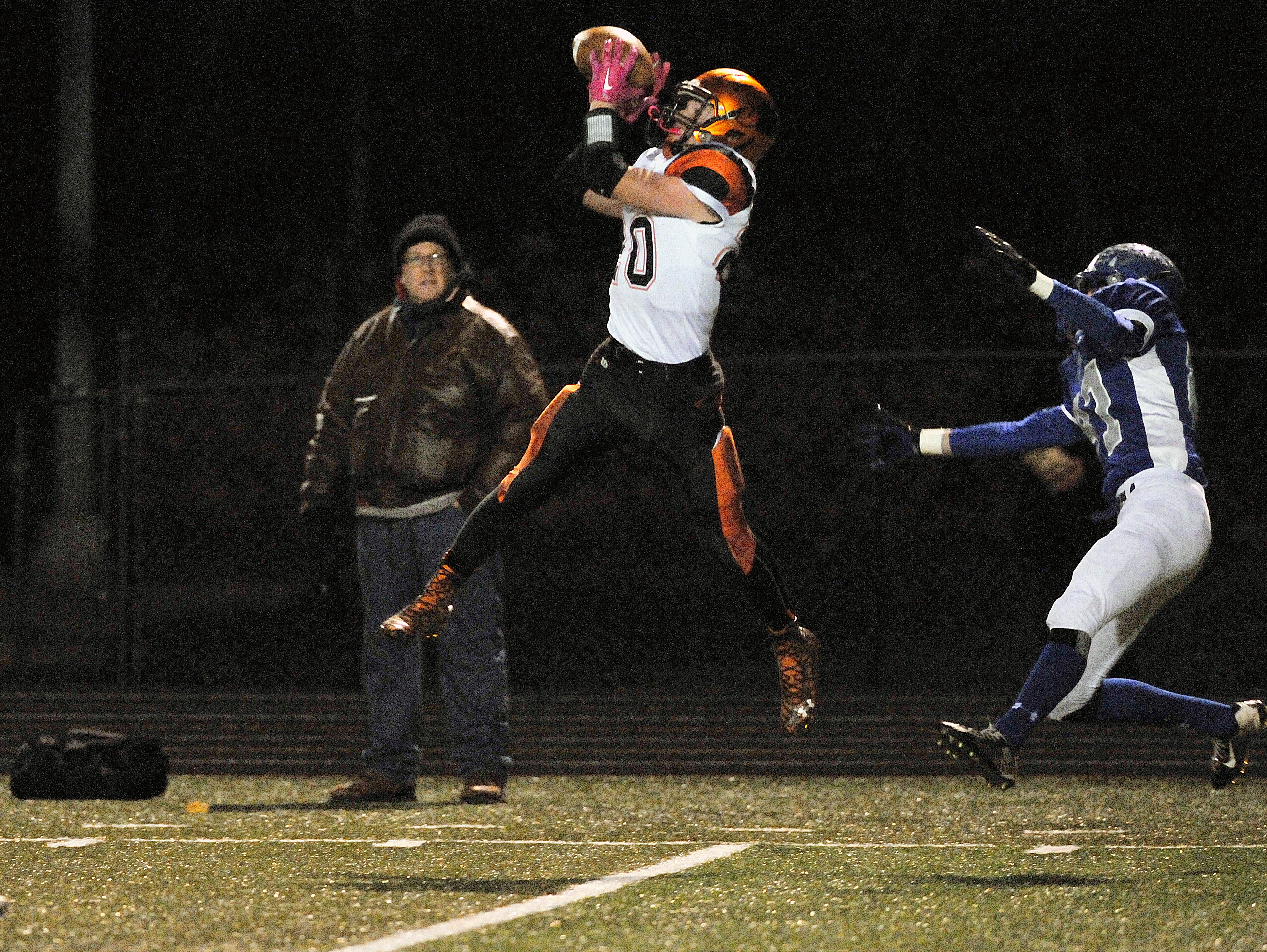 Lucas sophomore Jackson Hauger goes high to make a catch in the 44-35 regional semifinal win over two-time state champ Tiffin Calvert.