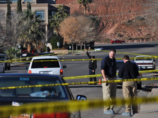 St. George Police investigators discuss a double murder case as police caution tape criss-crosses 600 South in St. George on Dec. 11, 2010.